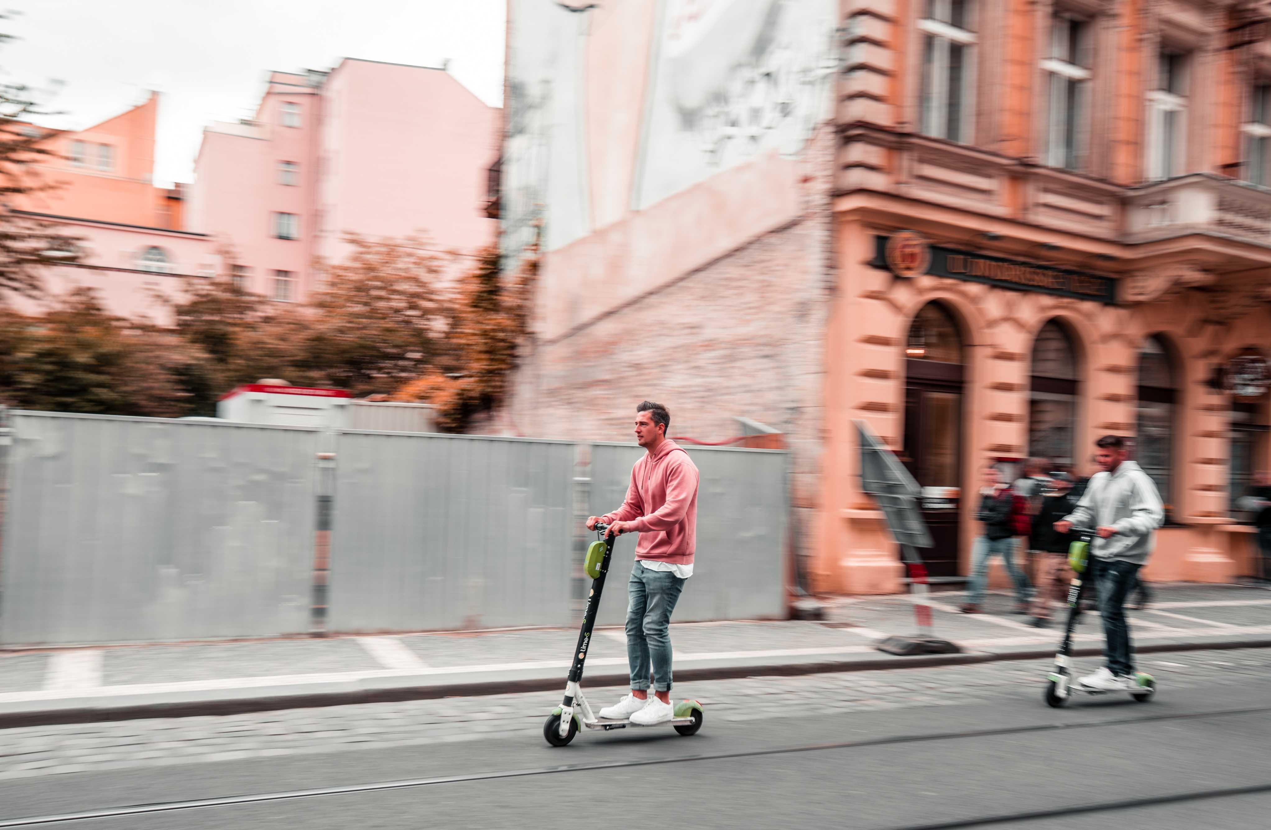Man op elektrische step in de stad